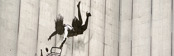 LONDON, UK - JUNE 15, 2015:  Banksy graffiti on the side of a disused office block in an expensive part of Central London showing a woman shopper falling with her shopping trolley and goods including a champagne bottle and pearl necklace.  On public display, viewed from pavement.